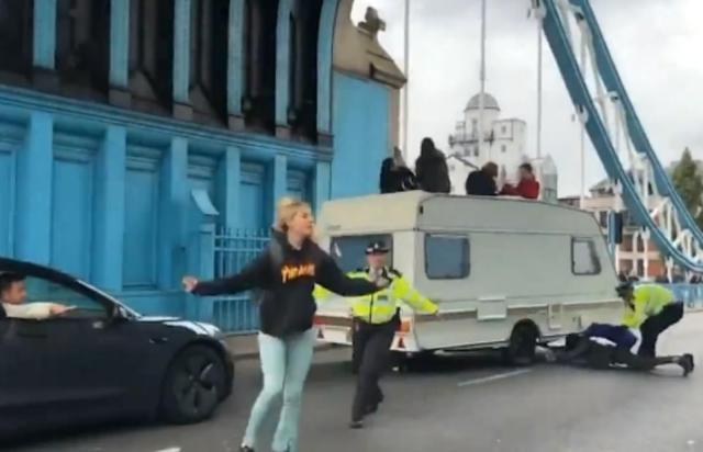 Speeded-up footage released by the group shows police grappling with scruffy members of the rag-tag protest running across the road with chains attached to their arms as frustrated drivers queue up waiting to cross