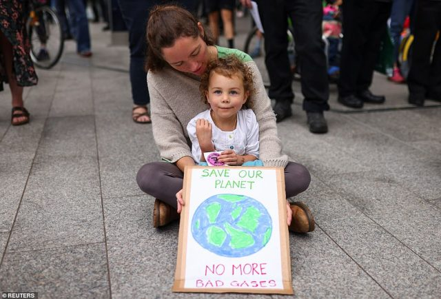 Willow-Rose Mitchell, 3, and her mother, Emma Mitchell sit on the ground with a placard, as they attend an Extinction Rebellion protest in London Bridge