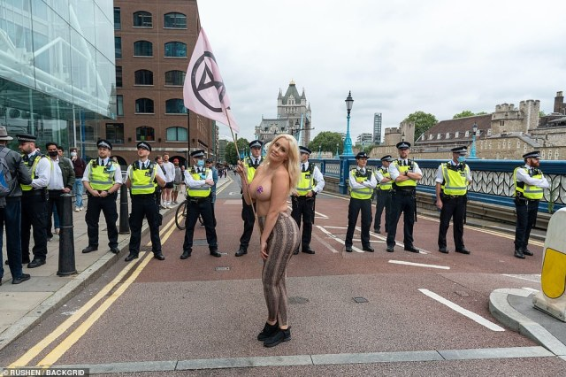 Topless vegan politics student and XR activist Laura Amherst stands in front of a line of police officers at Tower Bridge today