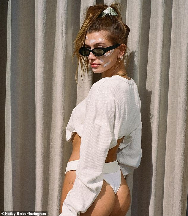 Cheeky: She's seen in a long-sleeve cropped, white thermal shirt and a white thick-banded thong