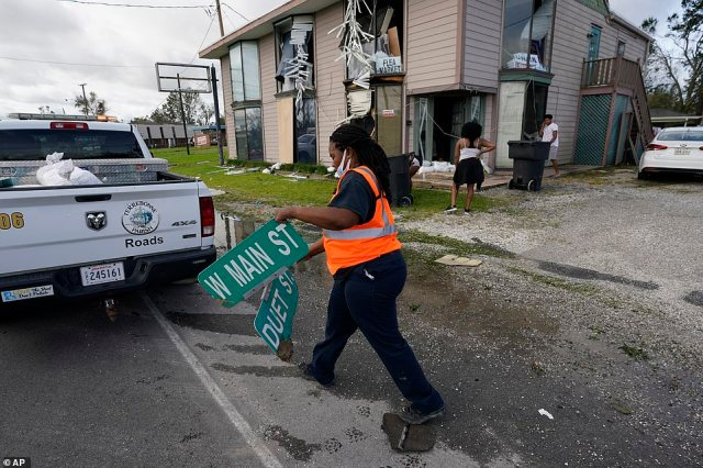 Worker Alissia Smith collects a fallen street sign in the aftermath in Houma, Louisiana