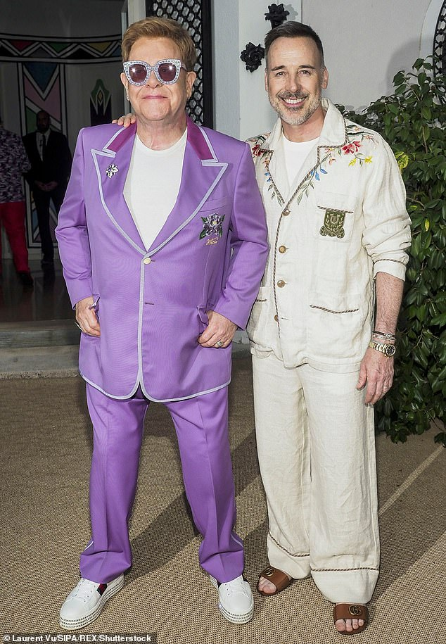 Even when he¿s dressing down, he¿s dressing up! Sir Elton John, 74, reveals he and his family wear matching £375 Versace gold-monogrammed robes at home