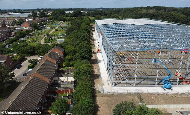 Families claim the 112,000 sq ft building (pictured), which will be completed shortly, has knocked up to £40,000 off the value of properties - and it is one of three being built behind homes