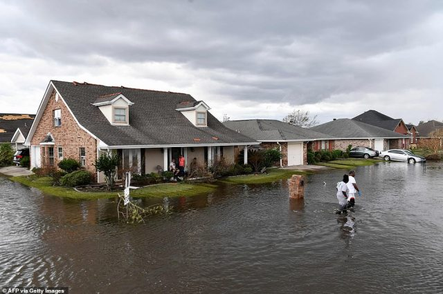 Residents wade through flood waters after their neighborhood flooded in LaPlace, Louisiana on Monday
