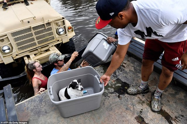 Volunteers Desiree Nye (left) and Hunter Louque help Darrin Heisser evacuate from his flooded home with his dog Sonny as they climb into a high water truck volunteering to evacuate people from flooded homes in LaPlace, Louisiana
