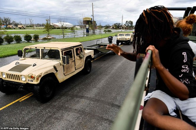 Kyler Melancon (right) waves at passing National Guard soldiers as he rides in the back of a high water truck in LaPlace, Louisiana