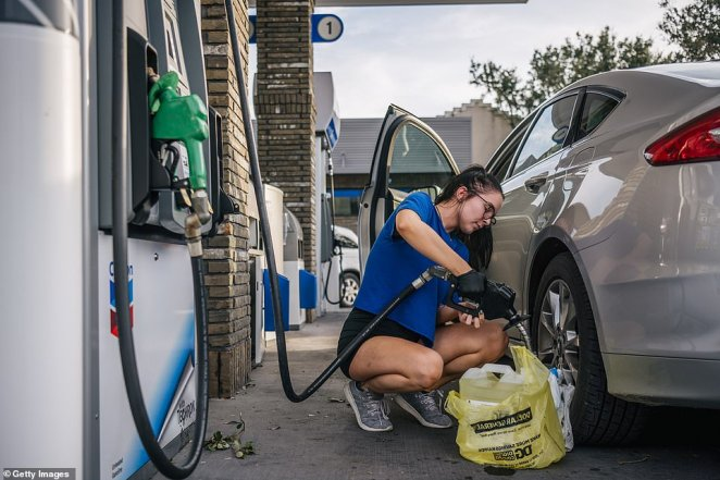 A woman pumps gas after Hurricane Ida passed through on August 30, 2021 in New Orleans, Louisiana. Many shops and stores are down as power throughout New Orleans is off