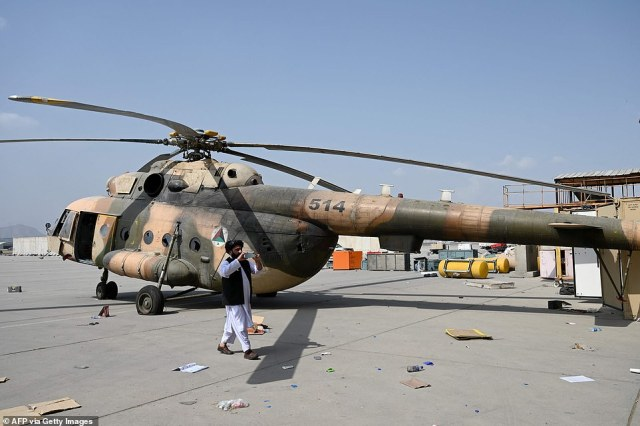 A RussianMi-17 helicopter is pictured alongside Taliban fighters after it was seized from retreating western troops