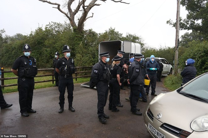 Uniformed officers wearing facemasks could be seen speaking to three people dressed in blue overalls and goggles outside the farm in Wickwar this morning, and tying rope around an animal