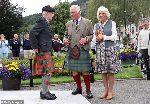 Dressed appropriately: Charles and Camilla both opted for a tartan kilt for their day out in Ballater. They are pictured talking to 90-year-old Hugh Inkster (left) as they visit a local shop during a walk through the village