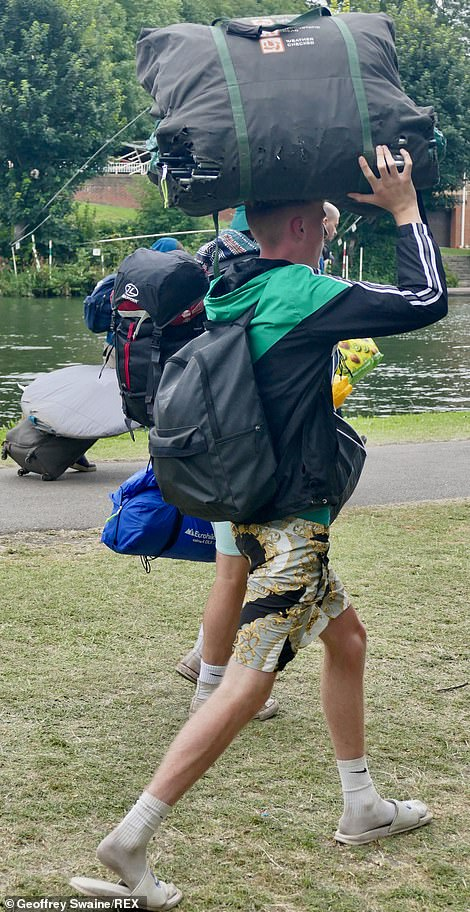 Heavy lifting: Festivalgoers laden with their weekend's worth of supplies left the venue in Berkshire on Monday morning
