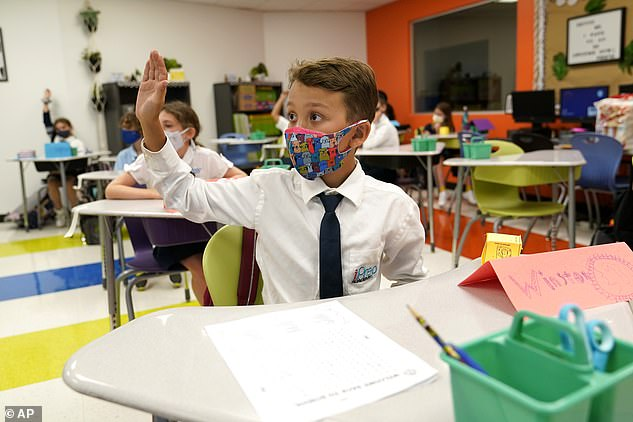 A masked student raises his hand in class at iPrep Academy on the first day of school in Miami last week. A judge has ruled that Florida school districts may impose mask mandates
