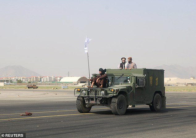 Taliban forces flying their flag drive down the runway at Kabul airport in an American Humvee after troops withdrew