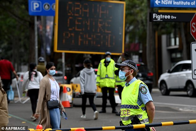 Australians may need to be triple-vaxxed about the latest strain (pictured Sydneysiders and police outside a vaccination hub)