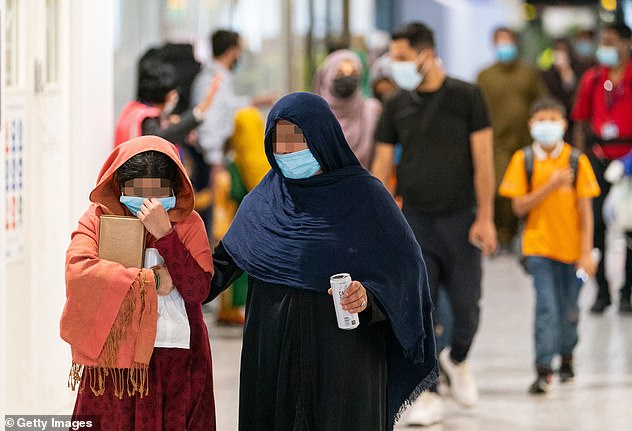 The Home Office said the coveted status would be granted immediately – and automatically – to around 10,000 refugees. Pictured: Afghan refugees arriving into Heathrow last week