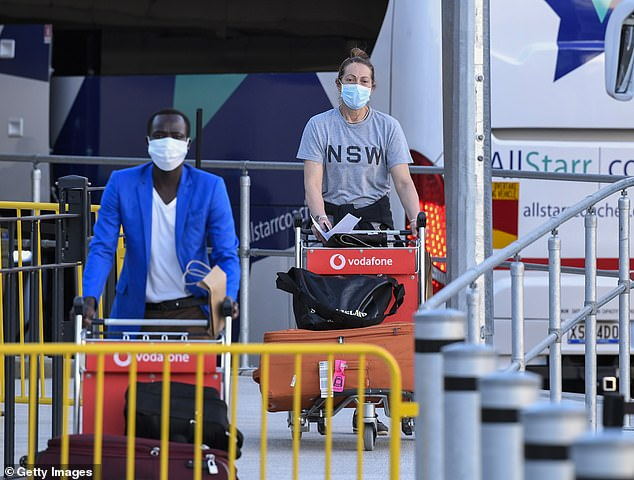 Passengers wearing facemasks arrive at Sydney International Airport off a Qatar Airways flight in May