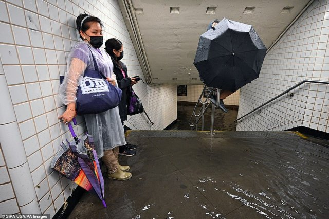 QUEENS, NEW YORK CITY: People stand inside a subway station as water runs past their feet during flash flooding caused by storm Ida