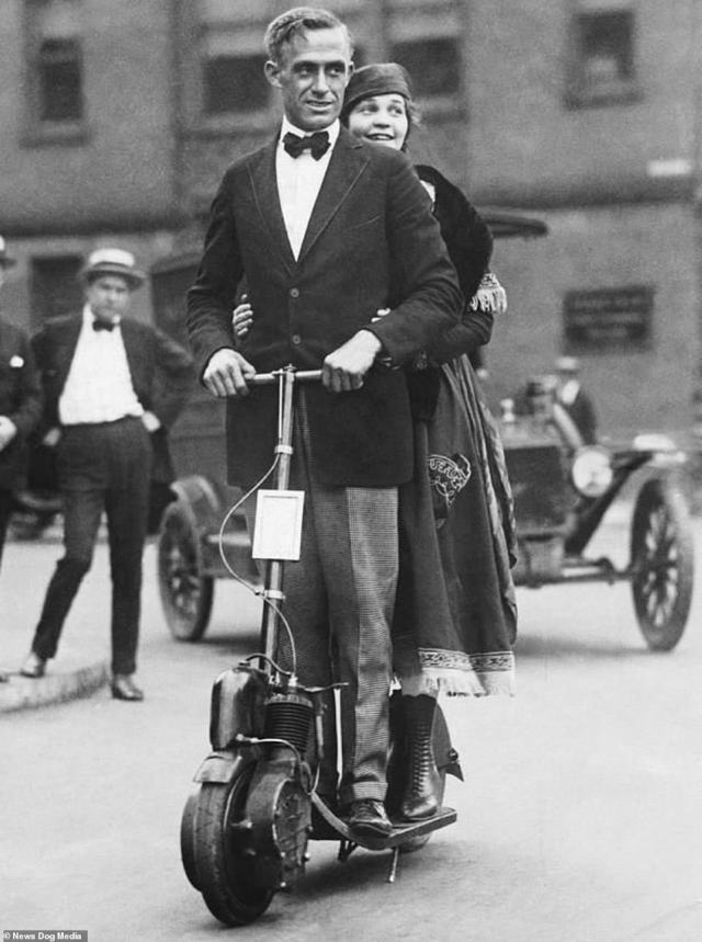 An American couple ride around on an Autoped scooter, circa 1918.While the majority of these scooters, known as Autopeds, were powered by petrol, electric versions were also made available to the Edwardian public