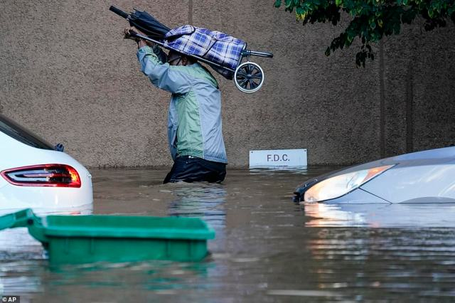 A person walks in floodwaters in Philadelphia, Thursday, Sept. 2, 2021 in the aftermath of downpours and high winds from the remnants of Hurricane Ida that hit the area