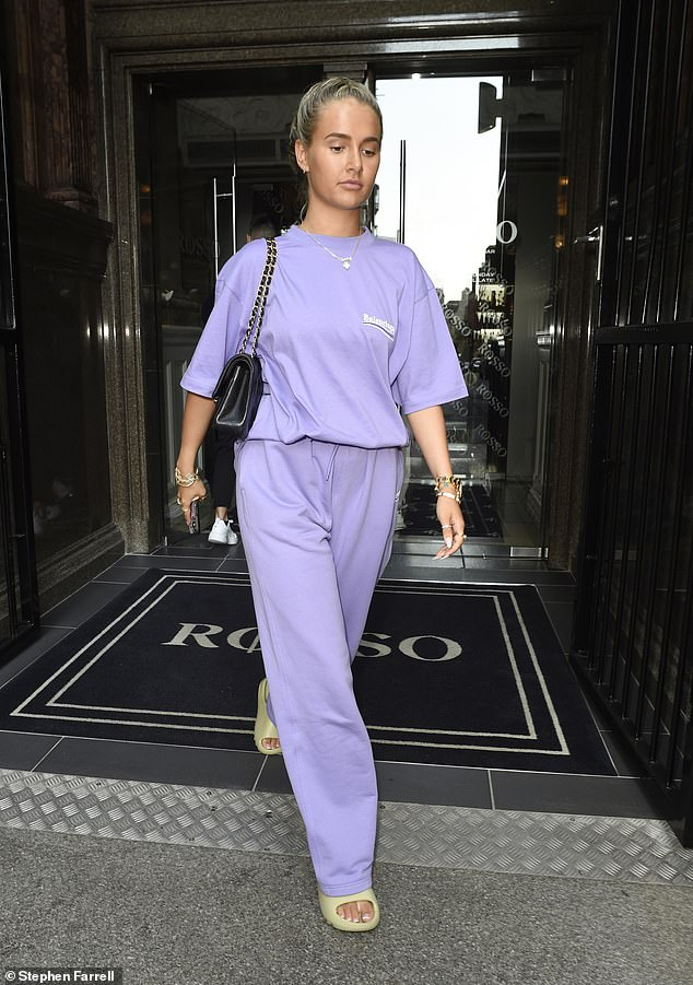 Keeping it casual: The influencer tucked a matching T-shirt into her purple trackies and wore her golden tresses in a sleek plait for the meal