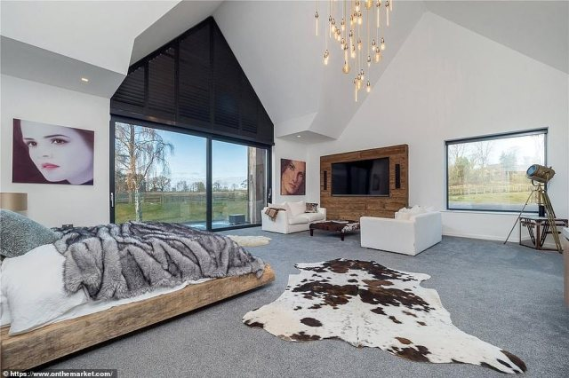 Ronaldo touched down in his private jet from Faro at Manchester Airport on Thursday at 5.40pm, and was swiftly taken to a multi-million pound mansion, according to the Sun. Pictured, the bedroom in the house features large windows and a TV built into the wall