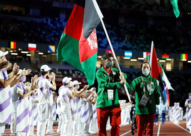 Hossain Rasouli of Afghanistan and Zakia Khudadadi of Afghanistan carry the flag of Afghanistan in the closing ceremony