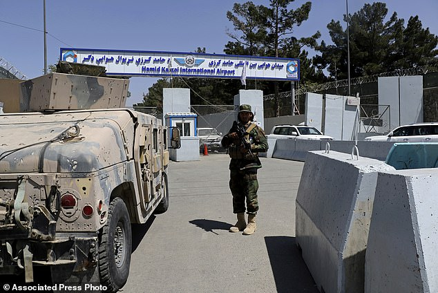 A Taliban soldier stands guard at the gate of Hamid Karzai International Airport in Kabul