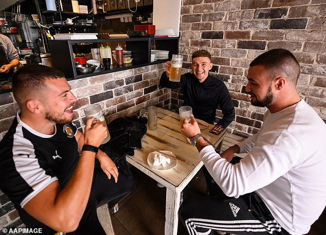 Thousands of Sydneysiders could enjoy a drink at the pub within weeks in a new government trial set to launch in one lucky suburb (pictured, men drinking in Bondi in May 2020)