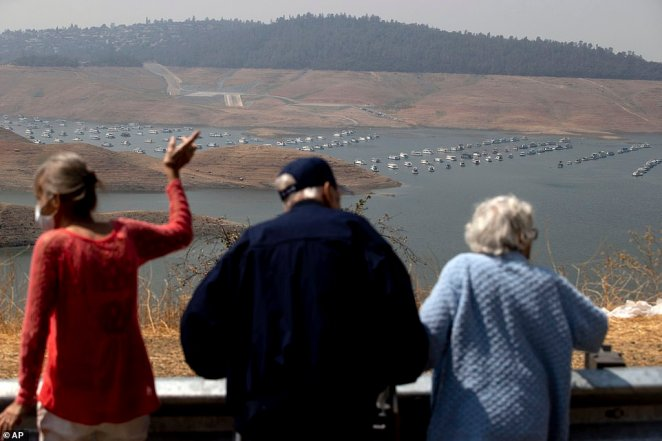 Visitors look out over Lake Oroville as water levels remain low due to continuing drought conditions in Butte County, Calif., Sunday, Aug. 22, 202