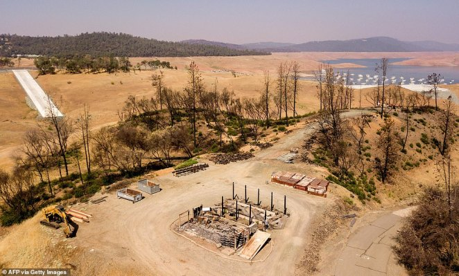 A burned property is seen over a depleted Lake Oroville in Oroville, California on September 5, 2021