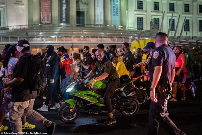 Partygoers smile as they walk and drive their motorcycles near the Brooklyn Museum on Monday