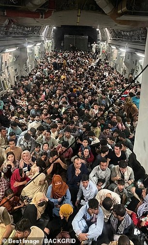 Afghan citizens pack inside a U.S. Air Force C-17 Globemaster III, as they are transported from Hamid Karzai International Airport in Afghanistan, Sunday, August 15, 2021