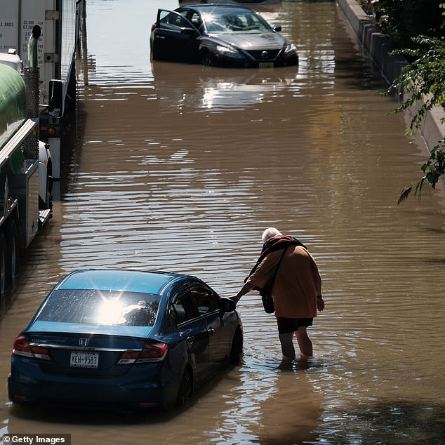 A person leans on an abandoned car on the flooded Major Deegan Expressway following a night of extremely heavy rain from the remnants of Hurricane Ida last Thursday in the Bronx