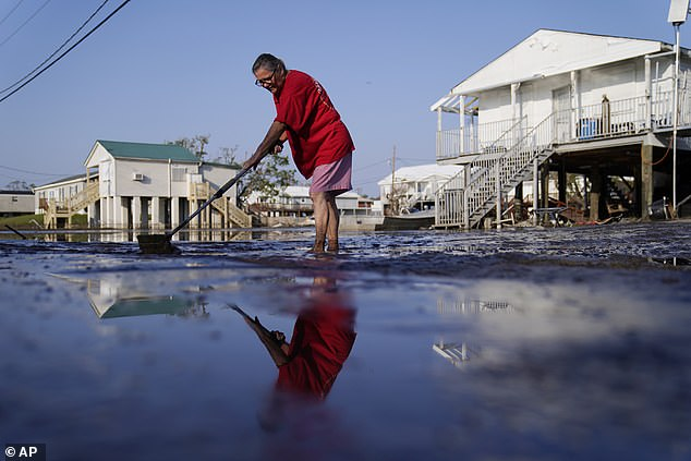 A woman in Lafitte, Louisiana clears floodwaters from her driveway on September 5