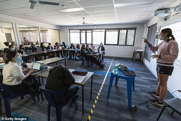A teacher is pictured wearing a mask as she teaches a class at Melbourne's Melba Secondary College on October 12. Victoria is aiming to get all students in their final year of high school vaccinated with at least one dose before their final exams