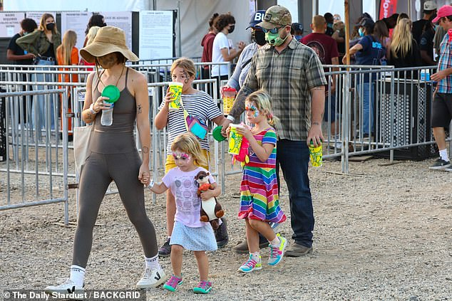 Family fun: The group could be seen carrying cups of refreshing lemonade as they walked while Minnie clutched a cuddly toy in her arms as they enjoyed Labor Day