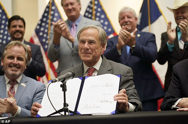 Texas Gov Greg Abbott shows off Senate Bill 1, also known as the election integrity bill, after he signed it into law in Tyler, Texas on Tuesday