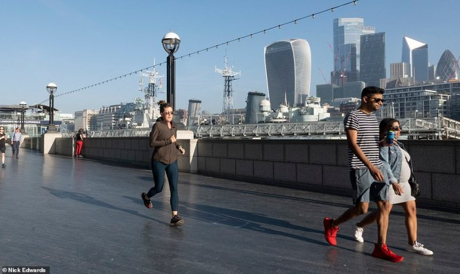 People head out to enjoy the warm sunny weather near Tower Bridge in London on Wednesday morning as temperatures are expected to hit 86F in some parts of the country