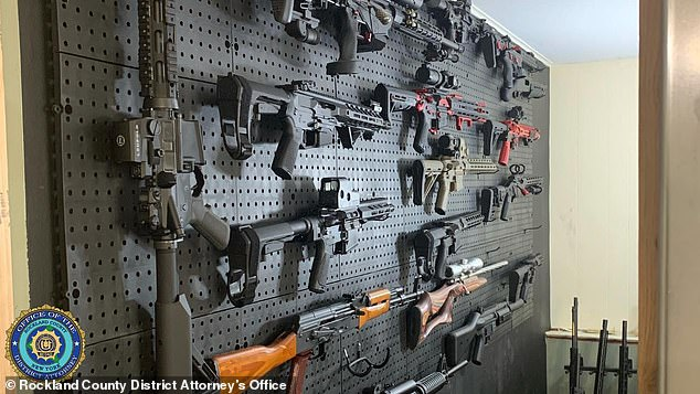 When authorities entered Downey's basement they discovered a black wall with over a dozen firearms displayed (pictured)