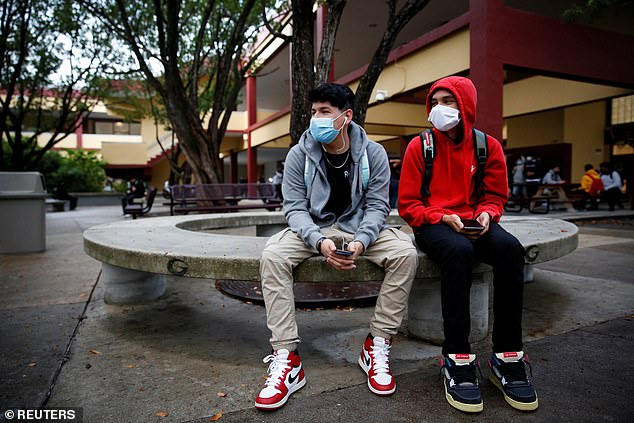 Schools in Florida, Texas, Arkansas and Arizona are not allowed to implement mask mandates according to statewide orders. Schools have become hotspots for the virus only weeks into the new school year. Pictured: Two Miami high school students wear masks on the first day of school