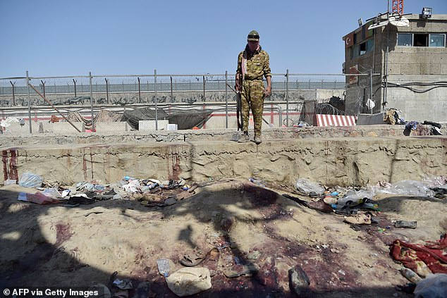 A Taliban fighter looks down into a blood-soaked canal around the airport perimeter where an ISIS bomber blew himself up and killed more than 180 people amid chaos after the fall of Kabul