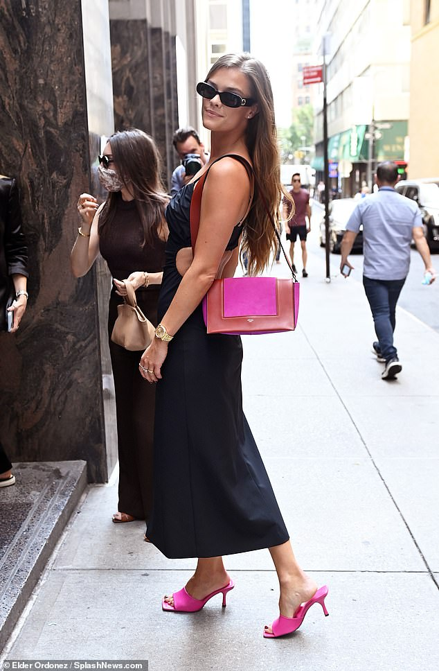 Next level:A pop of color took the ensemble up a notch as she added hot pink backless heels, and a matching hot pink and brown leather purse that she kept over her shoulder