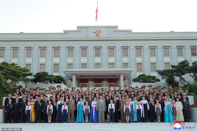 Pictured: Kim (centre in grey suit) and others pose for an official photograph to mark the 73rd anniversary of the foundation of North Korea