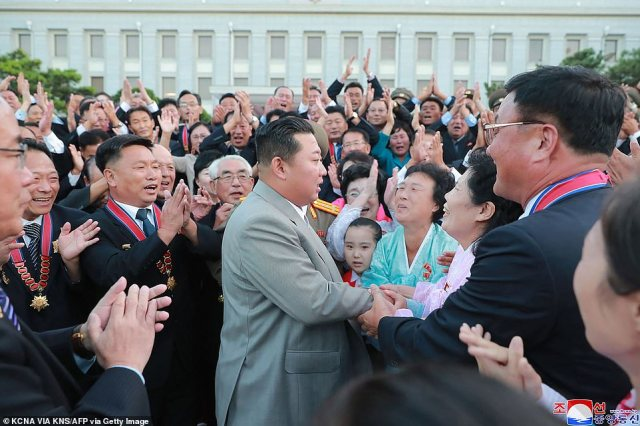 Pictured: North Korean leader Kim Jong Un (centre) greets attendees at celebrations to mark the 73rd anniversary of the country's founding