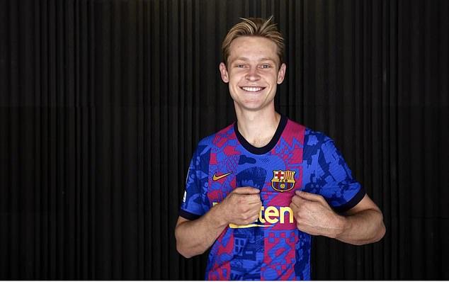 Midfielder Frenkie de Jong signals the club's badge as he models in the new design