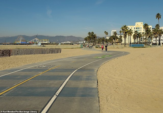 VIEW OF SANTA MONICA BEACH: 'The fancy oceanside homes remain, although in recent years some have been lost to high-tide damage and floods,' the author says of modern Santa Monica. Many of the piers that dotted the shoreline crumbled or burned down. The Santa Monica Pier is still standing, as is the pier's nine-story Pacific Wheel, which is 'the only Ferris wheel in California situated over the ocean'. Now, the beach – famed for its beautiful sunsets - is a hotspot for Los Angelenos, tourists, skateboarders and surfers, while surfers and swimmers take to the water