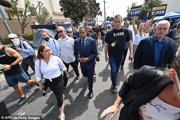 Conservative talk show host and gubernatorial recall candidate Larry Elder, flanked by supporters, security and media, walks along streets lined with tents of homeless people