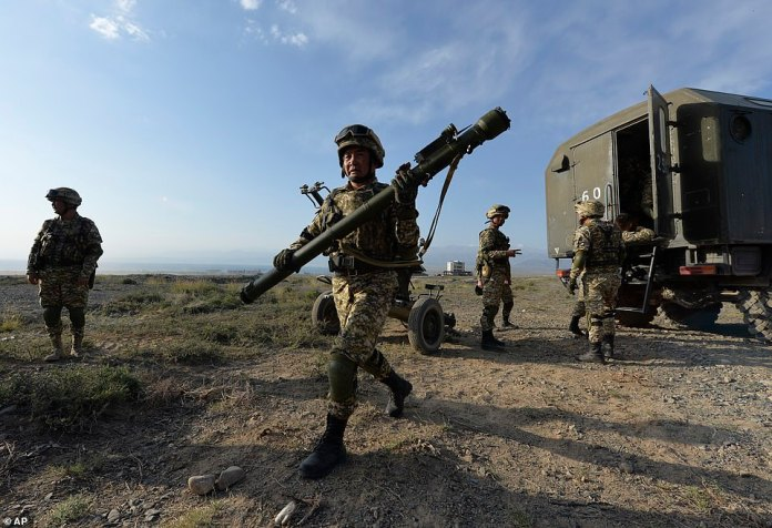 A Kyrgyzstan's soldier carries a portable air-defence system during mass military drills with Belarus and Russia being held across the countries' territories