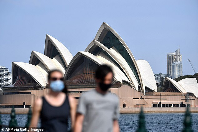 Pictured: People wearing face masks walk in front of the Opera House in Sydney on September 10, 2021, as Australia recorded a new record number of daily coronavirus cases