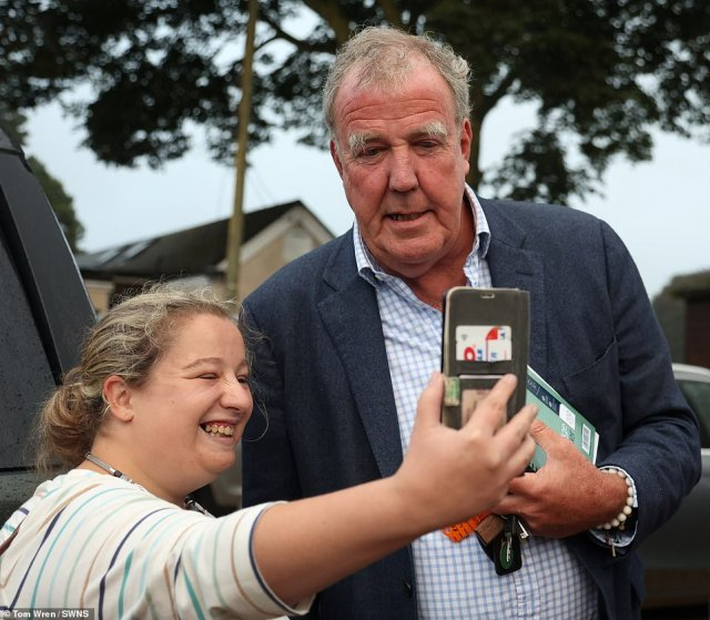 Jeremy Clarkson taking photos with locals ahead of his showdown with villagers angry over his popular farm shop